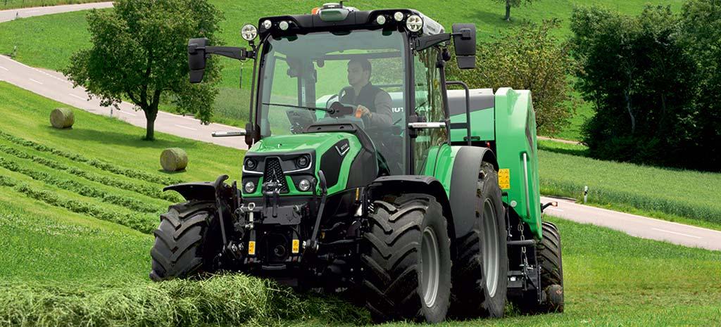 Landwirt presst Heu mit Traktor u. Rundballenpresse