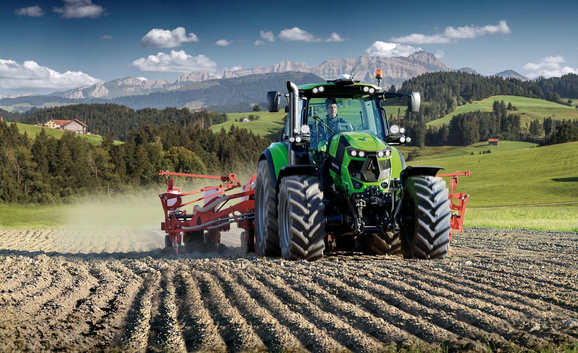 Traktor 6165 TTV Tier 4 Final mit einer Egge auf dem Feld