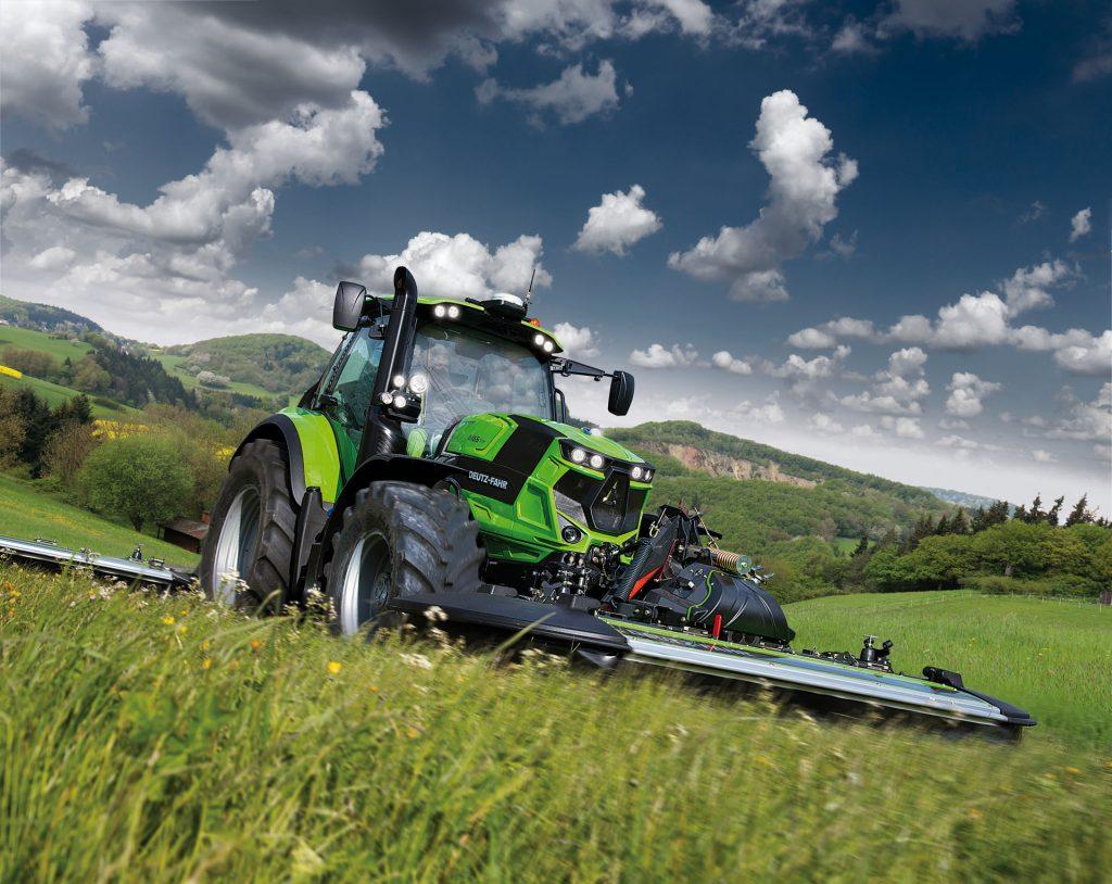 Traktor 6165 TTV Tier 4 Final mit Mähwerk auf einer Wiese
