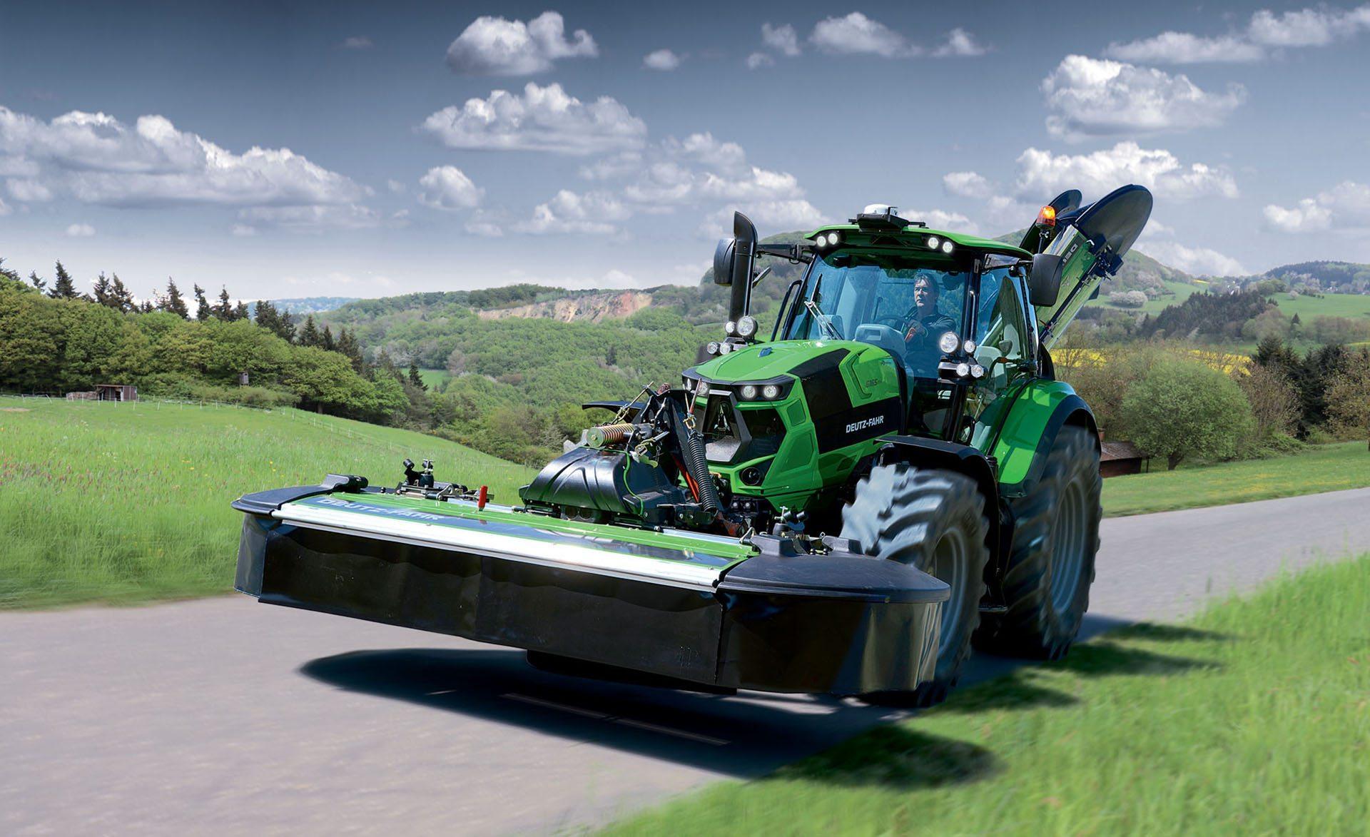 Traktor 6165 TTV Tier 4 Final mit Mähwerk auf einer Straße