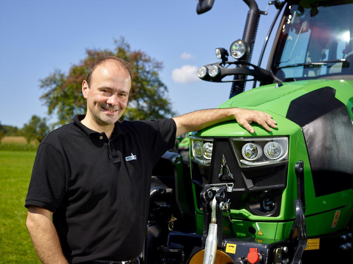 Produktexperte Martin Stögmüller steht links neben einem Traktor von Deutz-Fahr