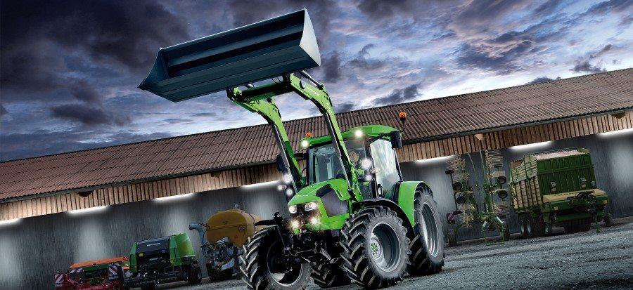 Traktor der Serie 5 mit hochgestelltem Frontlader, im Hintergrund weitere landwirtschaftliche Geräte
