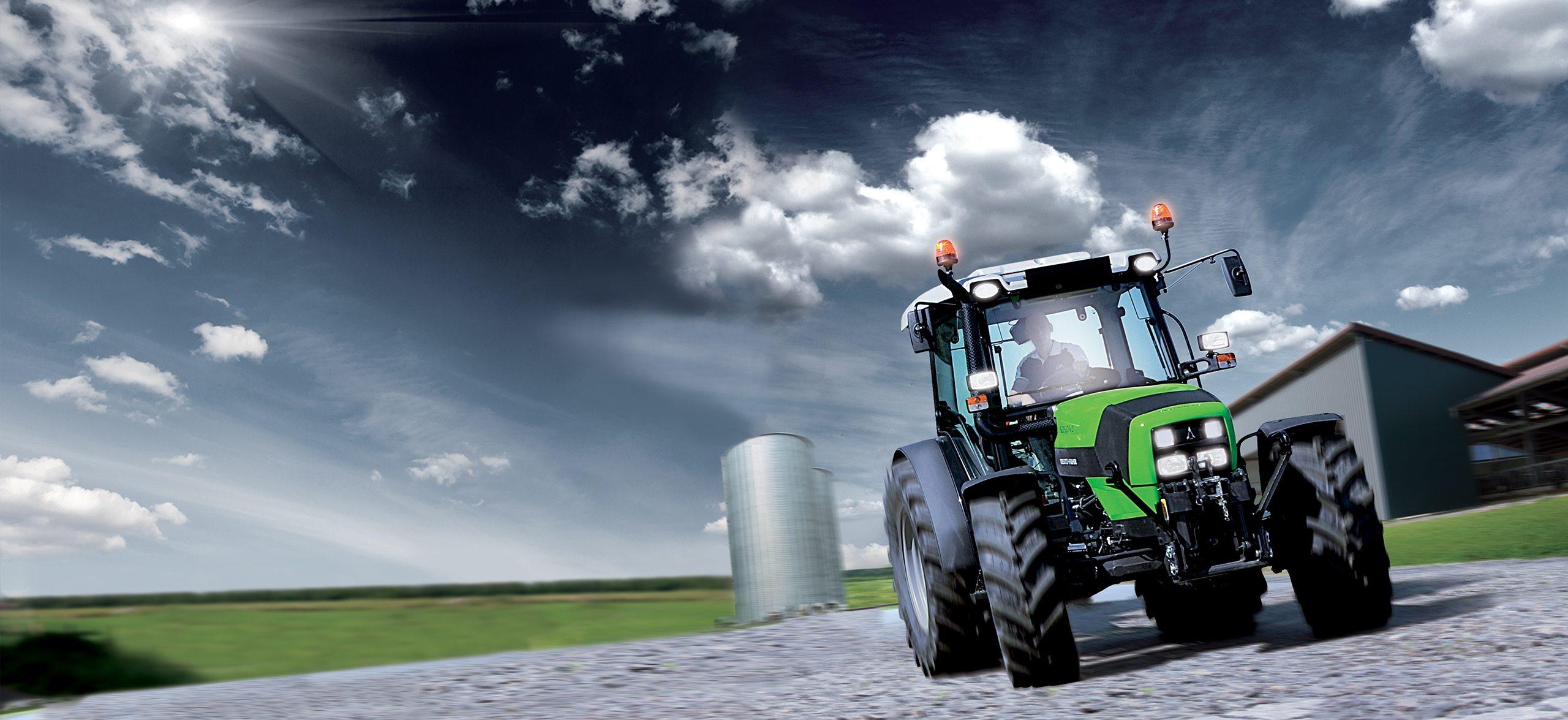 Traktor der Serie 5D, auf der linken Seite zwei Silos und auf der rechten Seite ein landwirtschaftliches Gebäude