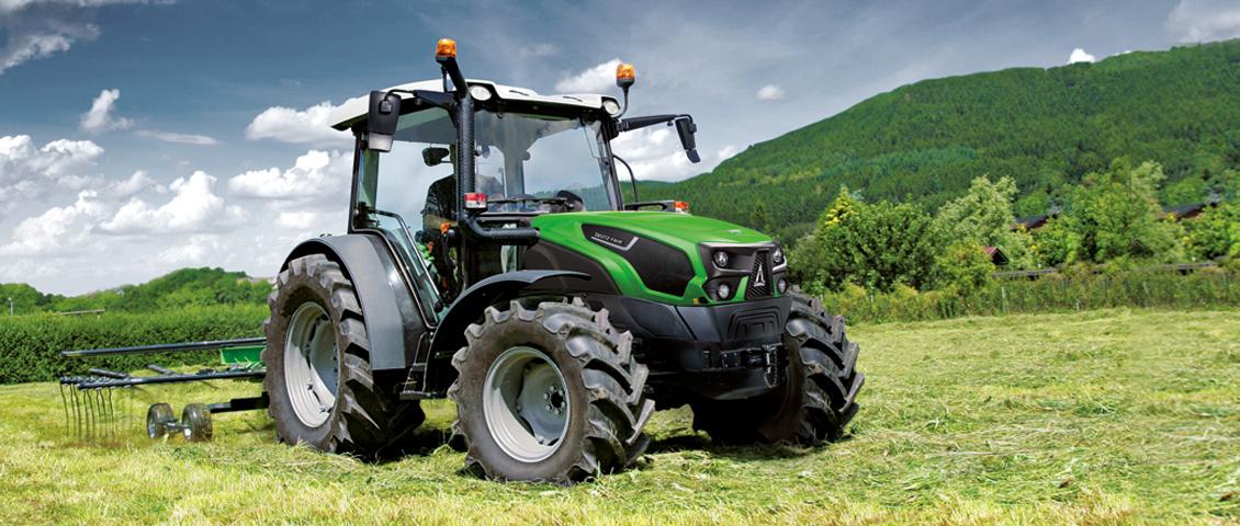 Landwirt schwadet Heu mit Traktor und Schwader auf der Wiese.