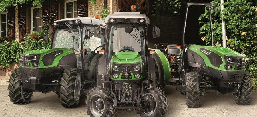 Drei verschiedene Traktoren der Serie 5 vor einem Bauernhof