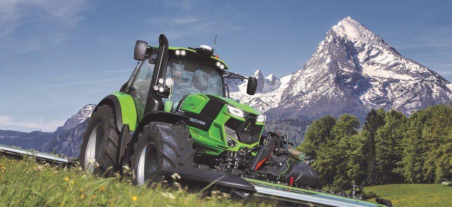 Landwirt fährt mit Traktor der Agrotron Serie 6.4 über eine grüne Wiese, im Hintergrund Bäume und ein hoher Berg
