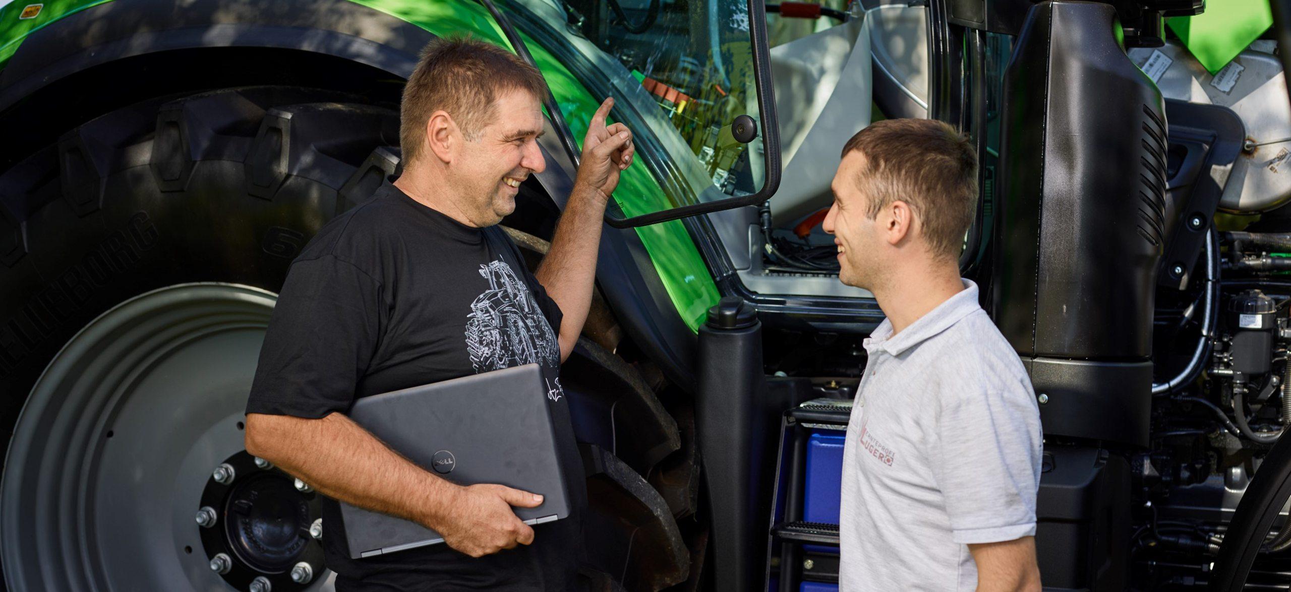 Servicetechniker erklärt im Beratungsgespräch einem Kunden Details zum Deutz-Fahr Traktor