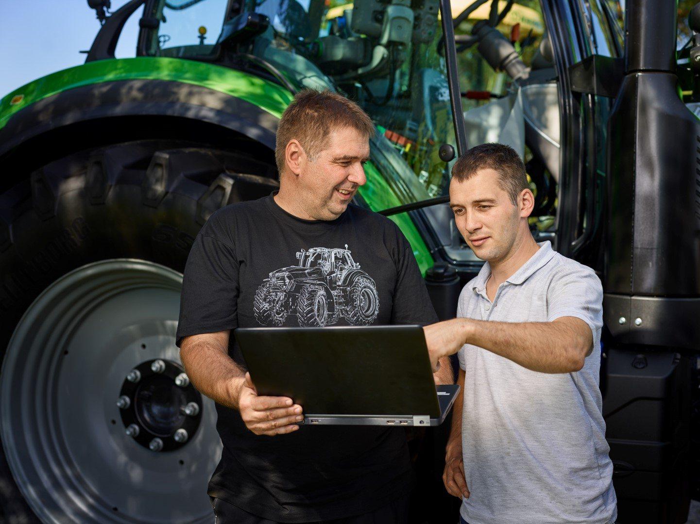 Servicetechniker mit Laptop erklärt im Beratungsgespräch einem Kunden Details über Deutz-Fahr Maschinen