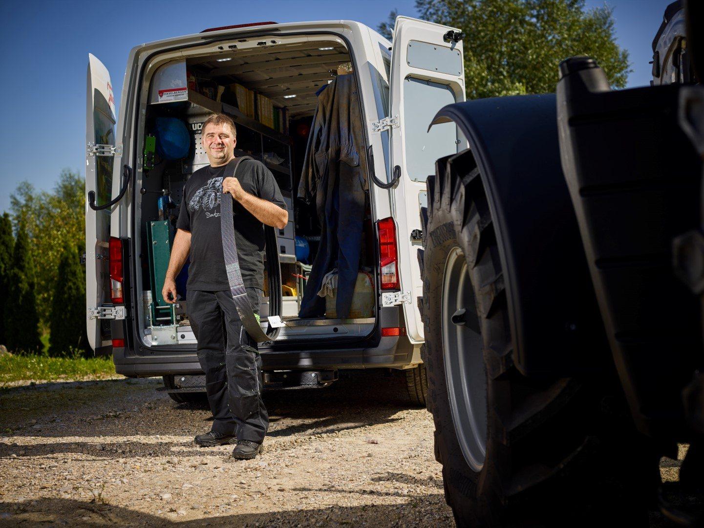 Servicetechniker vor dem Servicebus mit Ersatzteilen in der Hand